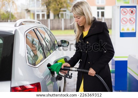 Young woman refilling petrol in gas station - stock photo