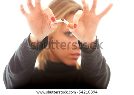 Young woman refuses to smoke and breaks cigarette. - stock photo
