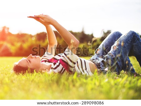 Young woman relax with her phone of coffee in city park - stock photo
