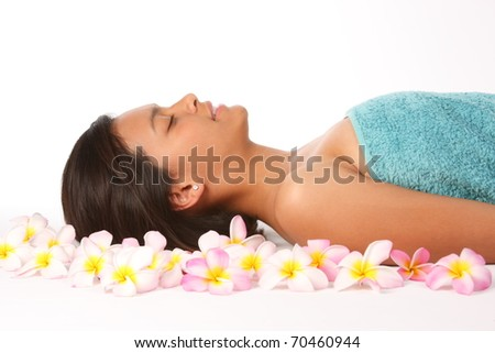 Young woman relaxed in health spa amongst tropical flowers