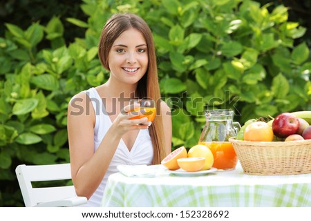 Young woman relaxes in the garden drinking a orange juice - stock photo