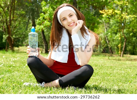 Young woman relaxing after sport in natural environment.