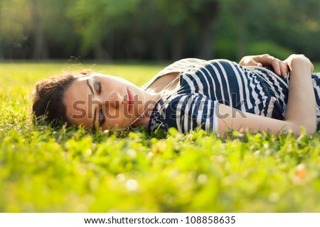 Young woman relaxing and listening to music outdoors