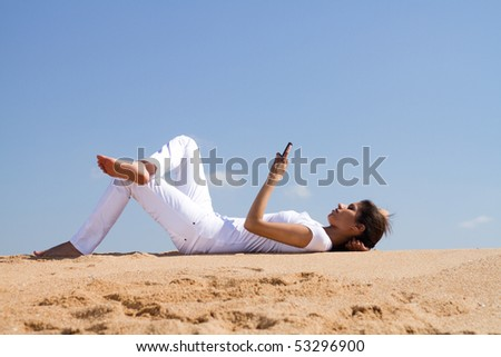 young woman relaxing and lying on beach reading sms from a cellphone - stock photo
