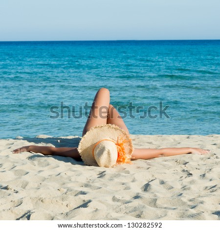 Young Woman Relaxing and Sunbathing At Beach - stock photo