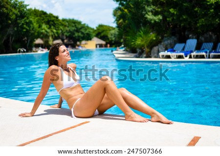 Young woman relaxing and tanning at resort poolside. Brunette caucasian model in white bikini enjoying summer vacation for resting and relax. - stock photo
