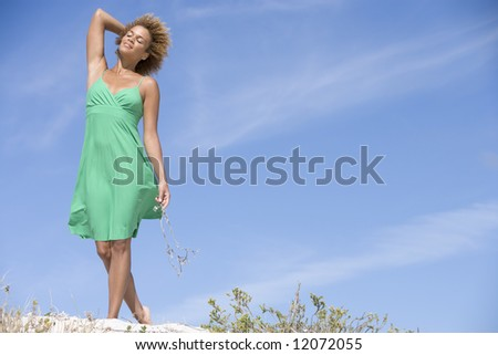 Young woman relaxing at beach against blue sky - stock photo