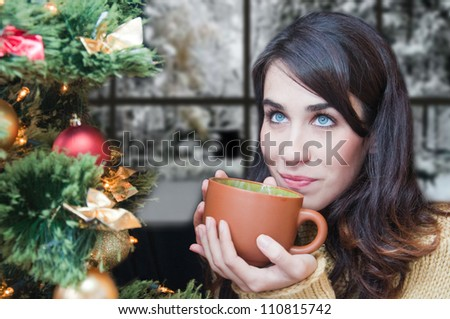 Young woman relaxing at home. Christmas time. Beautiful girl drinking tea at home. Winter day - stock photo