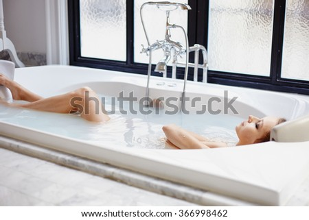 Young woman relaxing at the bathroom in bath in modern spa hotel - stock photo