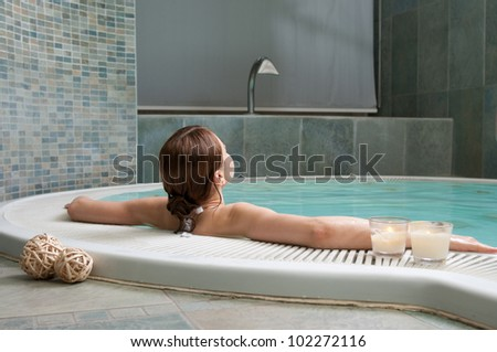 Young woman relaxing at the edge of a hot pool at spa center - stock photo