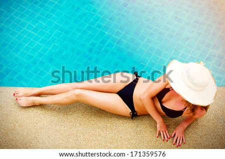 Young woman relaxing by the pool - stock photo