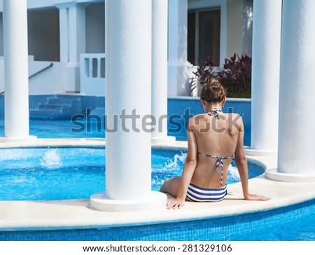 Young woman relaxing in a pool at summer - stock photo