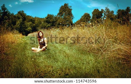 Young woman relaxing in a sunny field - stock photo