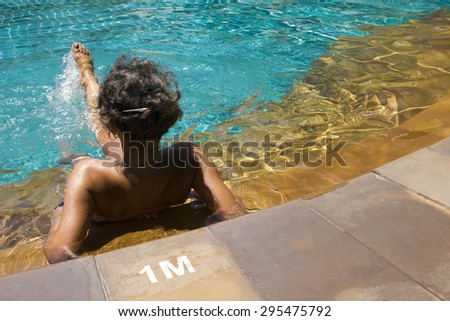 Young woman relaxing in a waterpool outdoors
