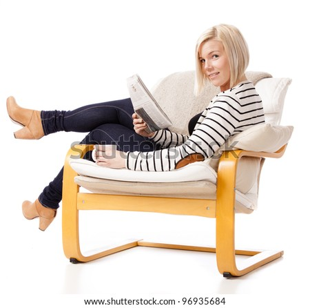 Young woman relaxing in an armchair reading the newspaper. She is looking into camera with a confident smile. She is very good looking. - stock photo