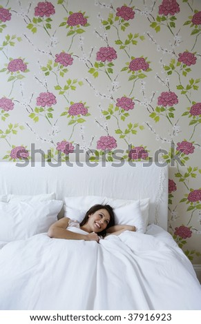 young woman relaxing in bed - stock photo