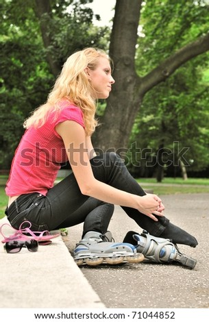 Young woman relaxing in park during rollerskating - trees in background