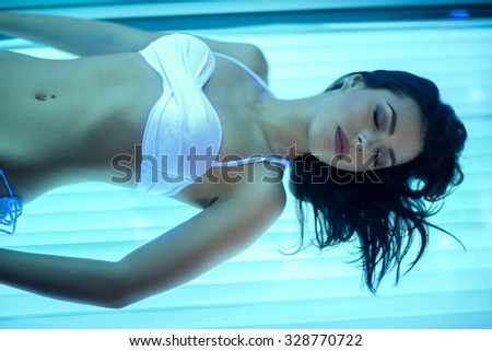 Young woman relaxing in solarium, have tanning skin treatment in bed solarium - stock photo