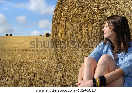 Young woman relaxing near the straw bales - stock photo