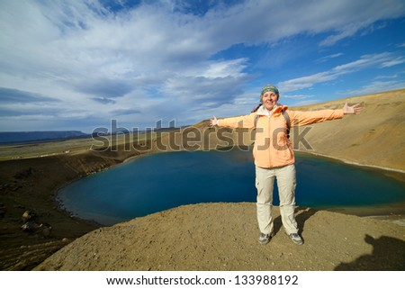 Young woman relaxing nearly the blue lake in the Viti crater in the Krafla region, northeast Iceland. Panorama - stock photo