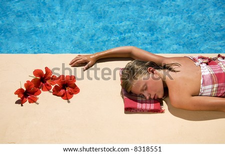 young woman relaxing next at the swimming pool side in a spa resort - stock photo