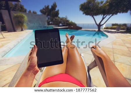 Young woman relaxing on a lounge chair using a tablet PC near the pool. User POV. Female model sitting on a deckchair holding digital tablet. - stock photo
