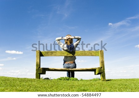 Young Woman Relaxing On A Park Bench On A Clear Summers Day