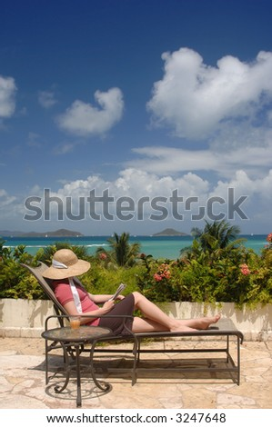 Young woman relaxing on a veranda with an aqua blue ocean and blue sky in the background