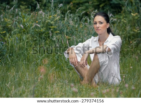 Young woman relaxing on meadow, outdoor. Adorable vitality girl sitting on grass, daylight - stock photo