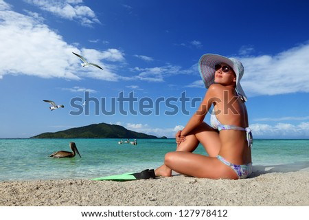 Young woman relaxing on the beach enjoying the flying birds against the green islands of the Caribbean - stock photo