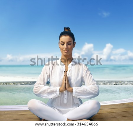 Young woman relaxing on the beach in prayer position, sitting eyes closed. - stock photo