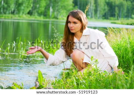 Young woman relaxing on the shore of lake. - stock photo