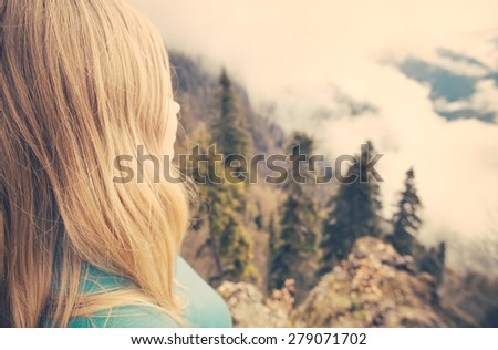 Young Woman relaxing outdoor on mountain summit with aerial view forest on background Lifestyle Travel concept Summer vacations  - stock photo