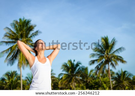 Young woman relaxing outdoor on tropical caribbean vacation to Mayan Riviera, Mexico. Relaxed brunette caucasian model enjoying vacation. - stock photo