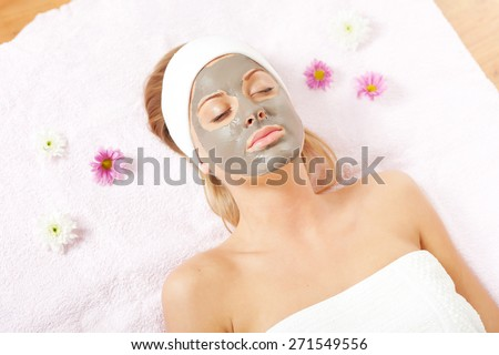 Young woman relaxing with clay skin mask on her face - stock photo