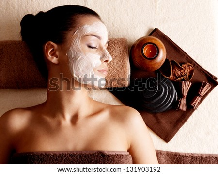 Young woman relaxing with facial mask on face at beauty salon- indoors - stock photo