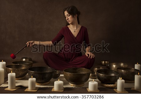 Young woman relaxing with Tibetan singing bowls in front of brown background - stock photo