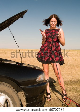 Young woman repairing car, connects cleats to the battery - stock photo