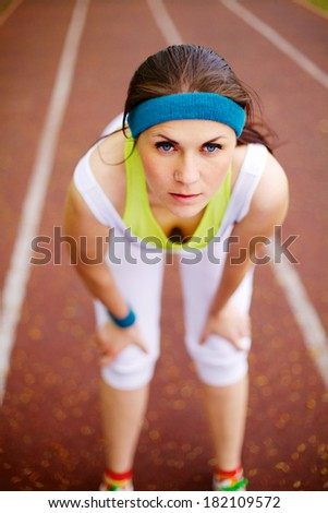 Young woman resting after run on outdoor stadium
