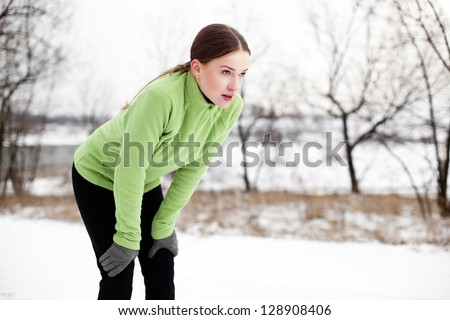 Young woman resting after running in winter - stock photo