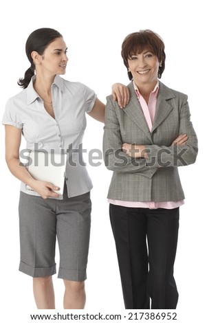 Young woman resting arm on mother's shoulder, holding tablet computer, both smiling. - stock photo