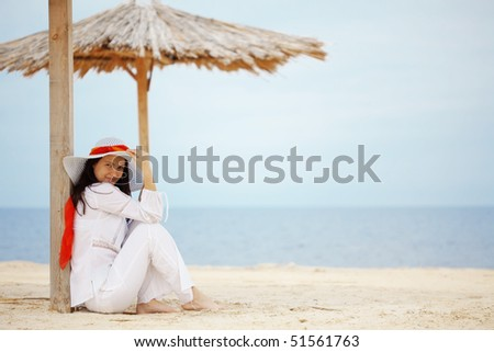 Young woman resting at beach near the sea - stock photo