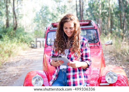 Young woman resting at car trip by the countryside