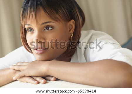 Young woman resting her chin on hands while thinking - stock photo