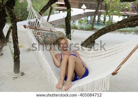 Young woman resting in a hammock. - stock photo
