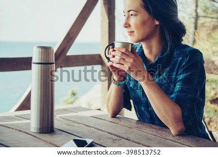 Young woman resting in wooden veranda in summer outdoor. Girl drinking tea in arbor