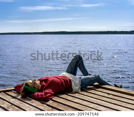 Young woman resting near the lake on a wooden pier in sunny day - stock photo