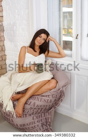 Young woman resting on bean bag chair at home, daydreaming, holding tea mug. - stock photo