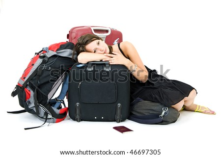 Young woman resting on her luggage, weary from traveling - stock photo