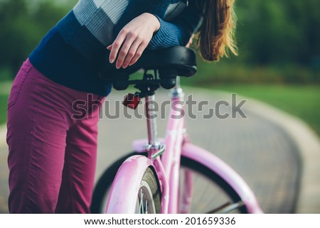 Young woman resting standing in park with bicycle